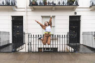 Carefree young woman jumping in front of city houses, London, UK - WPEF01649
