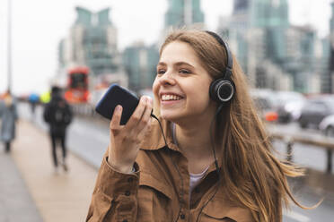 Happy young woman with headphones and cell phone in the city, London, UK - WPEF01652