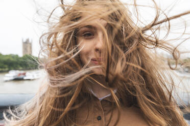 Portrait of smiling young woman with windswept hair, London, UK - WPEF01655