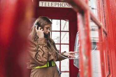 Young woma nmaking a call from a red phone booth in the city, London, UK - WPEF01658