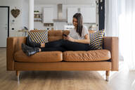 Young woman on couch at home using cell phone - GIOF06916