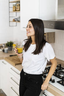 Young woman in kitchen at home drinking glass of orange juice - GIOF06922