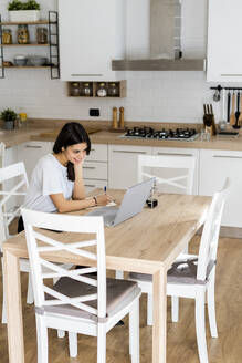 Young woman with laptop taking notes at home - GIOF06940