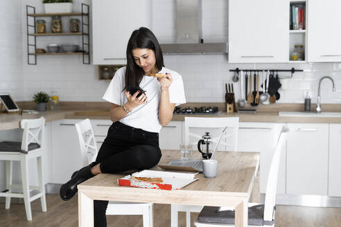 Young woman with cell phone eating pizza in kitchen at home - GIOF06949