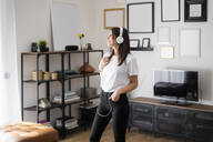 Happy young woman listening to music with headphones at home - GIOF06952