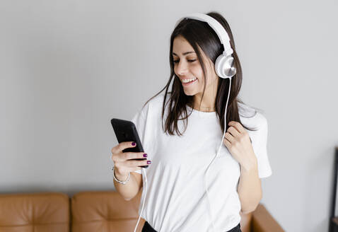 Happy young woman with smartphone and headphones at home - GIOF06955