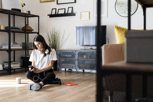 Young woman sitting on the floor at home using cell phone - GIOF06964