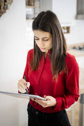 Young businesswoman using graphics tablet at home - GIOF06973