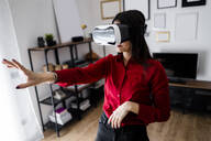 Young woman using VR glasses at home - GIOF06979