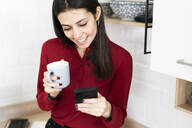 Smiling young businesswoman with cell phone and cup of coffee at home - GIOF06985
