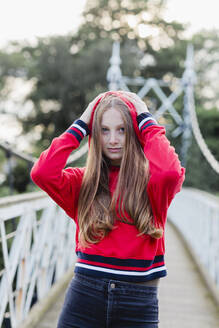 Portrait of teenage girl on a bridge, red hoodie sweater - NMS00374