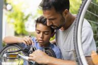 Deutschland, München, Vater 37 Jahre, Sohn 10 Jahre reparieren Fahrrad zusammen - DIGF07719