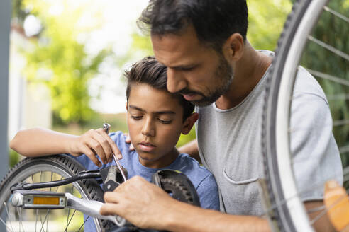 Father and son repairing bicycle together - DIGF07719