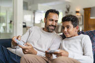 Happy father and son playing video game on couch in living room - DIGF07725