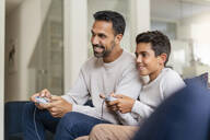 Happy father and son playing video game on couch in living room - DIGF07728
