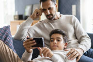 Father and son using smartphone on couch in living room - DIGF07731