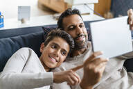 Happy father and son using tablet on couch in living room - DIGF07734
