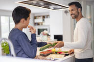 Father and son cooking in kitchen at home together - DIGF07740