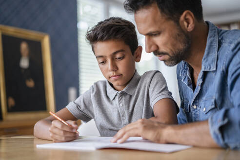 Father helping son doing homework - DIGF07743