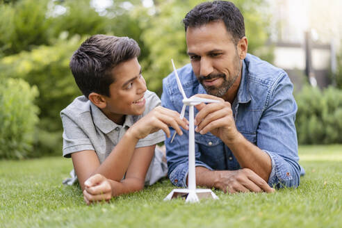 Smiling father and son lying in garden with a wind turbine model - DIGF07749