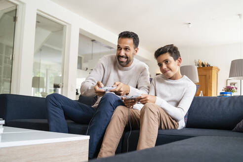 Happy father and son playing video game on couch in living room - DIGF07758