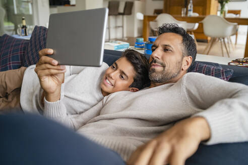 Happy father and son using tablet on couch in living room - DIGF07761