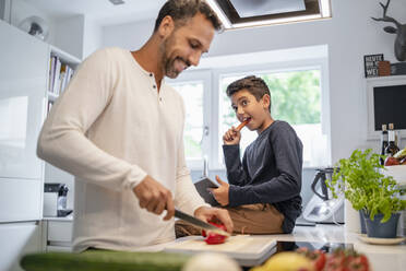 Father and son cooking in kitchen at home together - DIGF07773