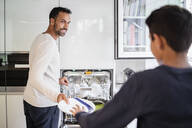 Father and son in kitchen clearing dishwasher together - DIGF07776