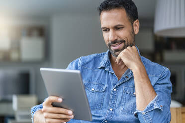 Smiling man using tablet at home - DIGF07782