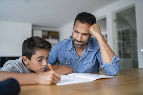 Father helping son doing homework - DIGF07785