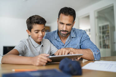 Father and son using tablet and doing homework - DIGF07788