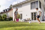 Father and son playing football in garden - DIGF07791