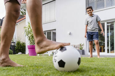 Father and son playing football in garden - DIGF07794