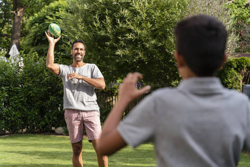 Father and son playing with american football in garden - DIGF07797