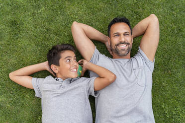 Happy father and son lying in grass together - DIGF07800