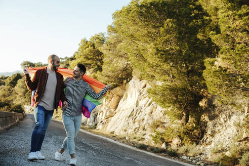 Gay couple with gay pride flag walking on a road in the mountains - LJF00501