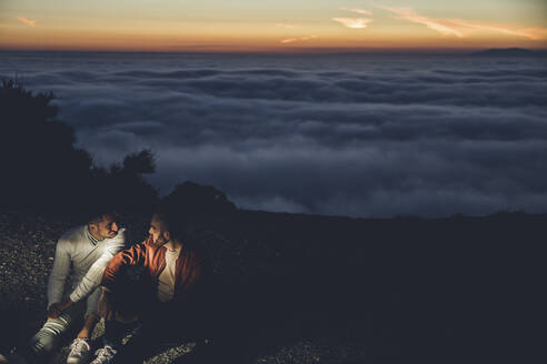 Gay couple sitting in the mountains above the clouds at sunset - LJF00516