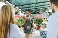 Happy worker in a garden center showing plants to customers - JRFF03448