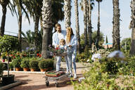 Happy family buying plants in a garden center wth the daughter in shopping cart - JRFF03457