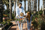 Happy family buying plants in a garden center wth the daughter in shopping cart - JRFF03460