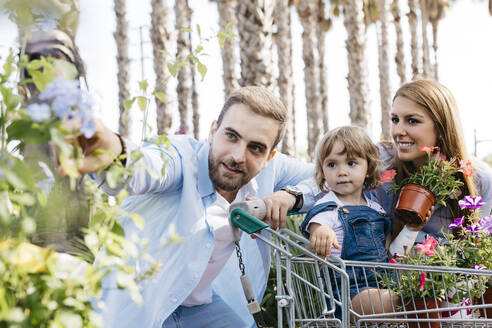 Happy family buying plants in a garden center wth the daughter in shopping cart - JRFF03469