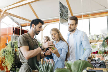 Shop assistant in a garden center advising customers - JRFF03487