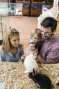 Happy family looking at rabbits in a pet shop - JRFF03499
