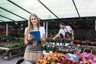 Portrait of a smiling female worker in a garden center using a tablet - JRFF03505