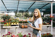 Portrait of a smiling female worker in a garden center holding a tablet - JRFF03514