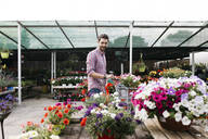 Customer of a garden center looking at plants - JRFF03520