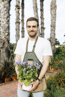 Portrait of a smiling worker in a garden center holding a lilac plant - JRFF03538