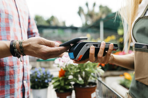 Close-up of customer paying with smartphone in a garden center - JRFF03541