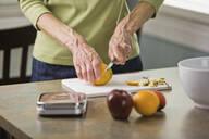 Senior woman cutting fruit - BLEF12274