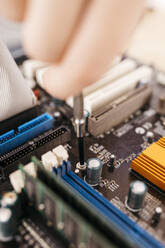 Close-up of technician repairing a desktop computer, using a screwdriver - JRFF03544
